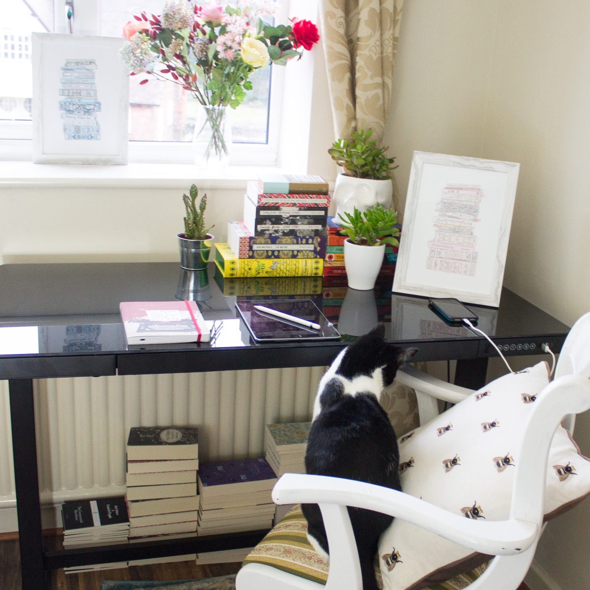 Black and white cat at a writing desk with stacks of books