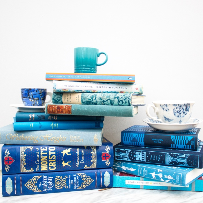 Stack of blue classic books with espresso cups and tea cups